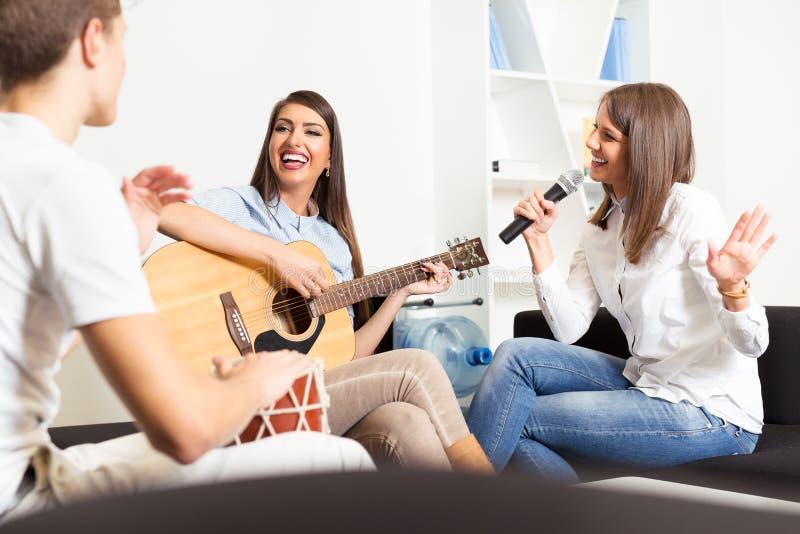 Amigos que gozan tocando la guitarra y cantando junto imagen de archivo