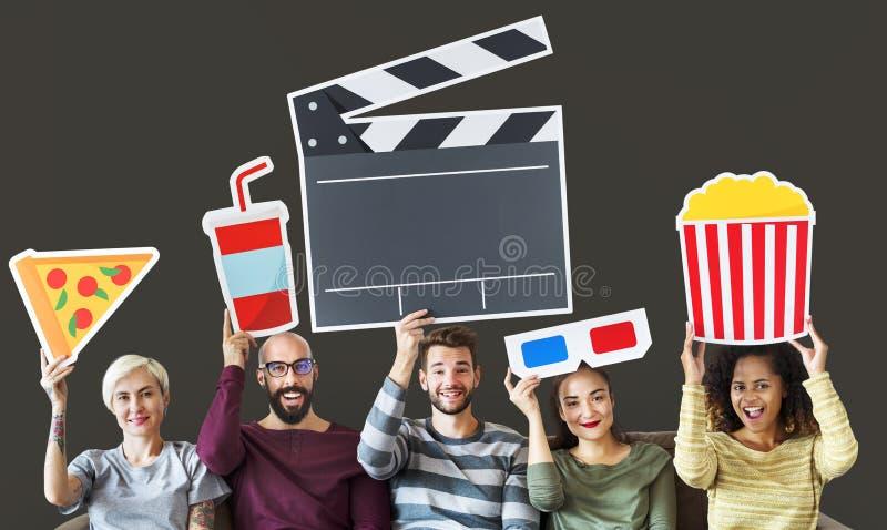 Amigos que guardam o ícone do filme ao sentar-se no sofá imagens de stock royalty free