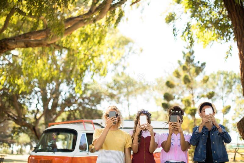 Amigos que guardam o telefone esperto na frente da cara fotos de stock