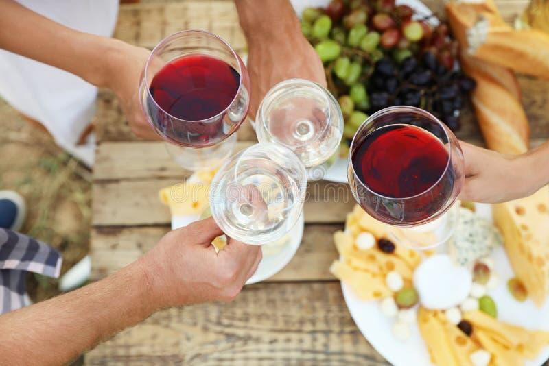 Amigos que guardam vidros do vinho sobre a tabela de piquenique no vinhedo imagens de stock royalty free