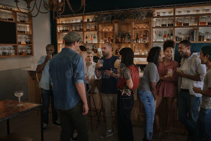 Amigos que hablan y que beben junto en una barra en la noche imagenes de archivo