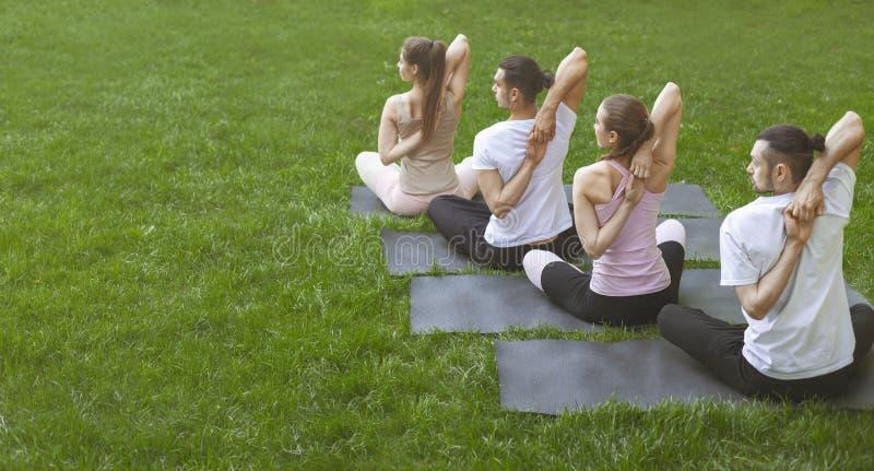 Amigos que hacen ejercicios de la yoga con las manos enganchadas detrás de la parte posterior imagenes de archivo