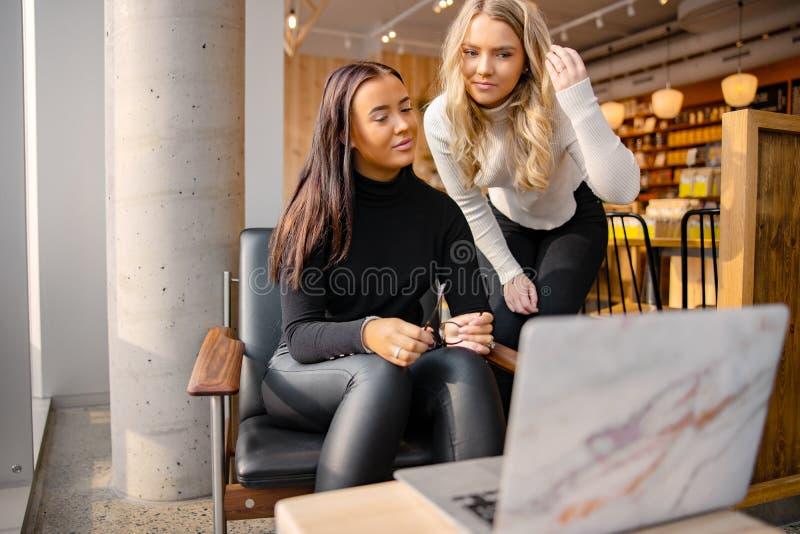 Amigos que hacen Schoolwork en el ordenador portátil en el restaurante en ciudad imagenes de archivo