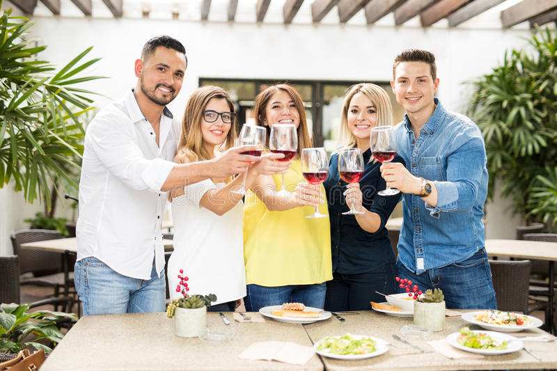 Amigos que hacen una tostada con el vino foto de archivo libre de regalías