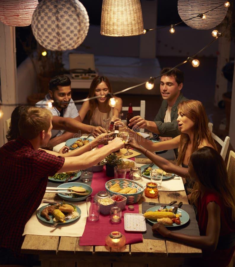 Amigos que hacen una tostada en un partido de cena del patio, vertical imágenes de archivo libres de regalías