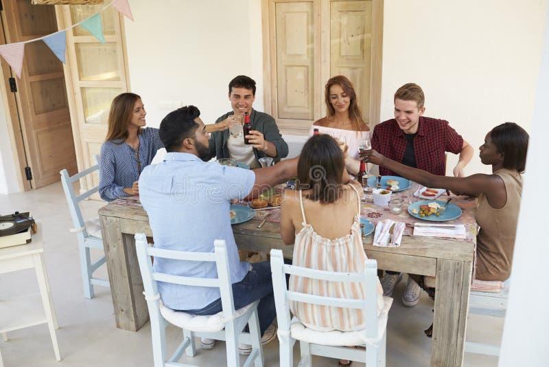Amigos que hacen una tostada en un partido de cena en un patio, Ibiza fotos de archivo
