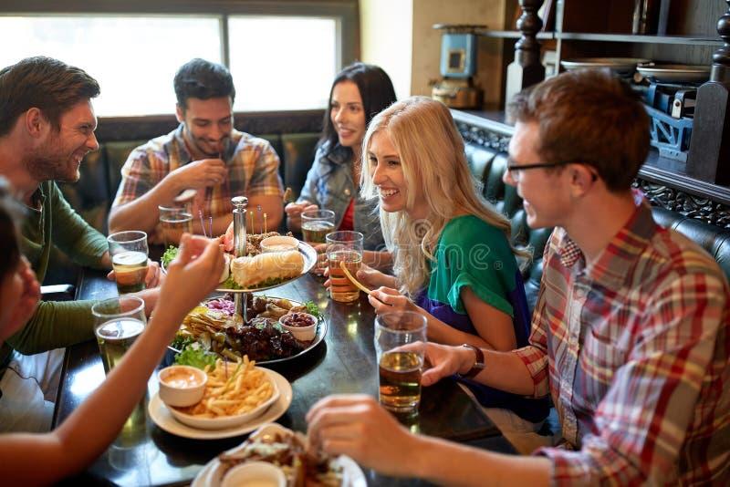 Amigos que jantam e que bebem a cerveja no restaurante imagens de stock
