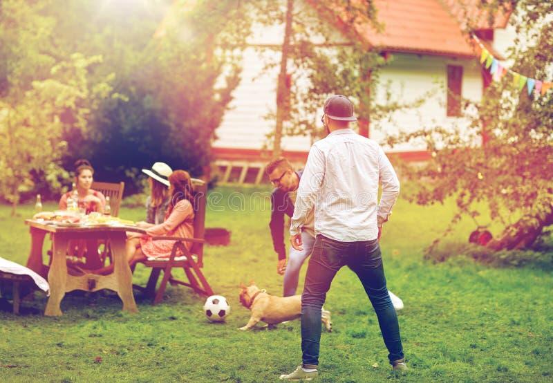 Amigos que jogam o futebol com o cão no jardim do verão fotografia de stock