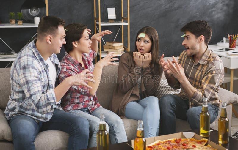 Amigos que jogam o partido do jogo da testa em casa imagens de stock royalty free
