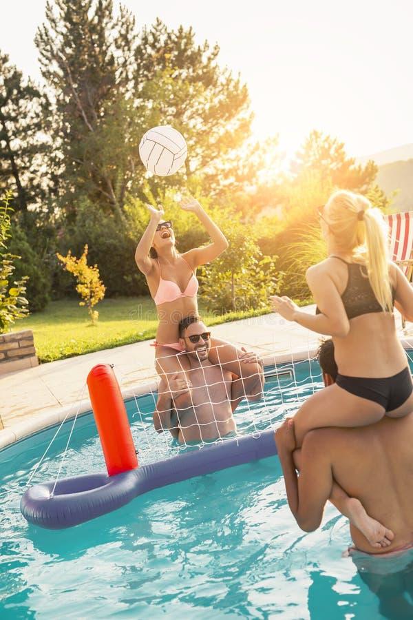 Amigos que jogam o voleibol em um partido de piscina fotografia de stock
