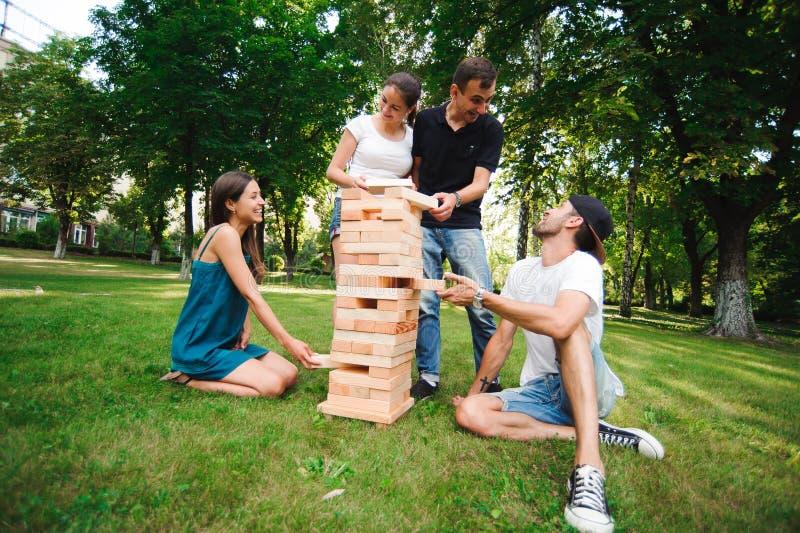 Amigos que juegan al juego de mesa Juego al aire libre gigante del bloque Juego del grupo de la habilidad física con los bloques  imagen de archivo libre de regalías