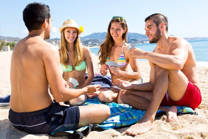 Amigos que juegan el póker en la playa fotos de archivo