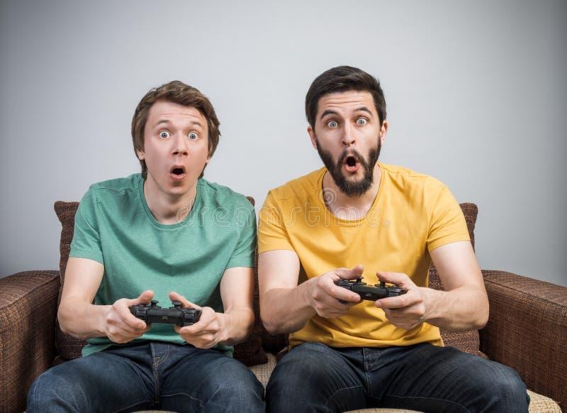 Amigos que juegan a los juegos video imagen de archivo