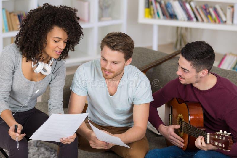 Amigos que juegan música en casa imagen de archivo libre de regalías