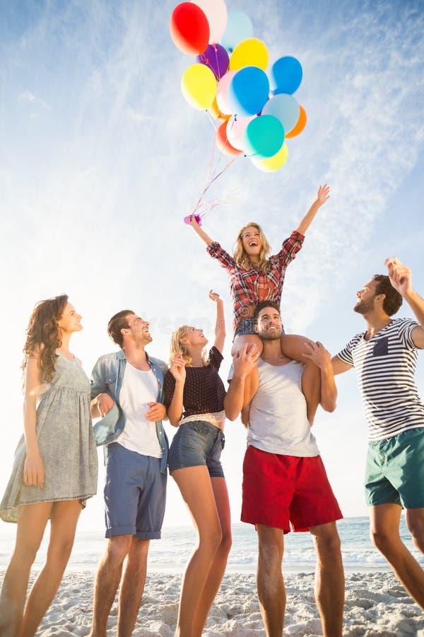 Amigos que levantam com o balão na areia imagem de stock