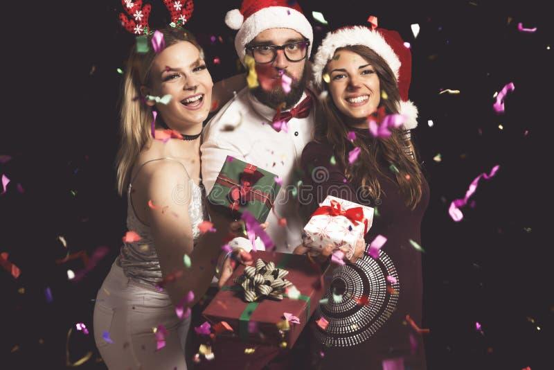 Amigos que llevan a cabo regalos de Navidad foto de archivo libre de regalías