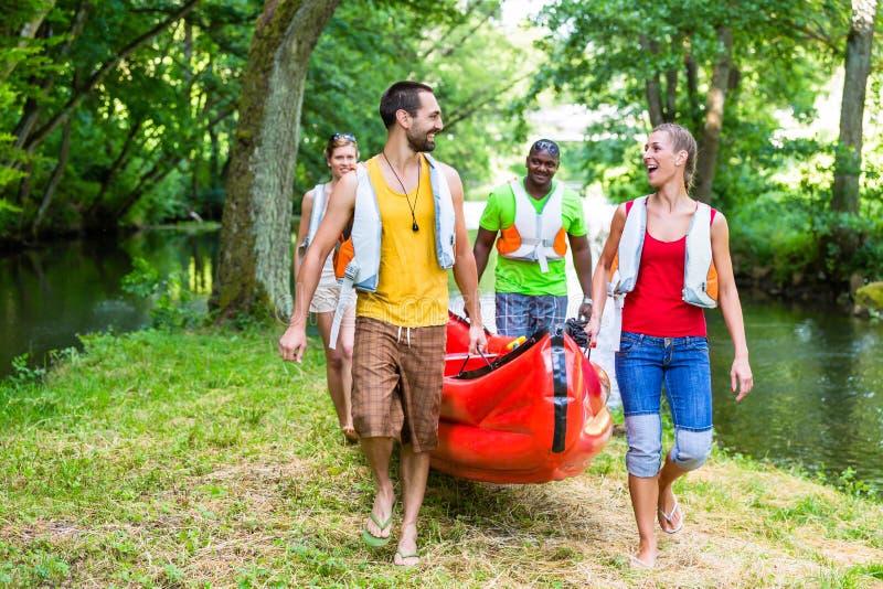Amigos que llevan el kajak o la canoa al río del bosque imágenes de archivo libres de regalías