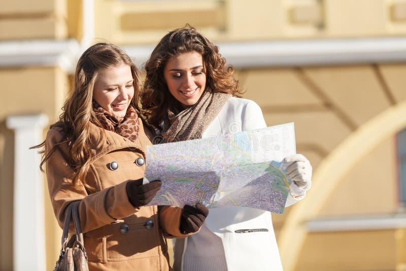 Amigos que miran el mapa. Dos mujeres jovenes hermosas que miran adentro imágenes de archivo libres de regalías
