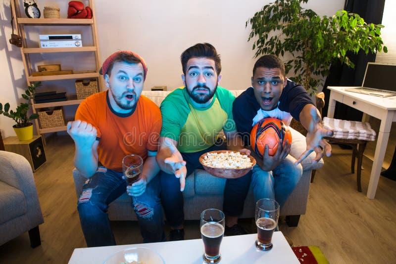 Amigos que miran el partido de fútbol imagen de archivo libre de regalías