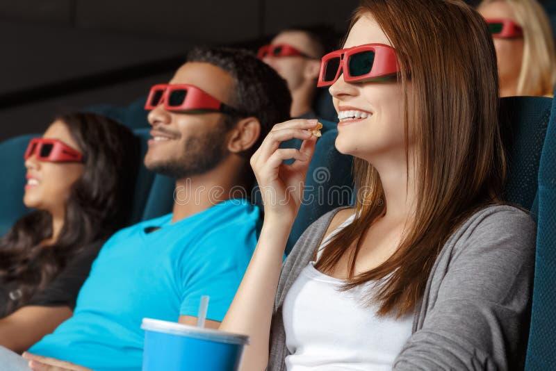 Amigos que miran la película 3D imagenes de archivo
