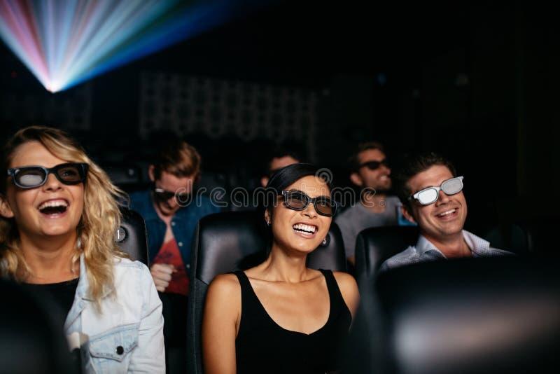 Amigos que miran la película 3d en teatro y la risa fotografía de archivo libre de regalías