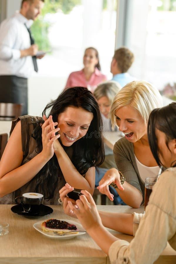 Amigos que miran las fotografías y que ríen el café imagen de archivo