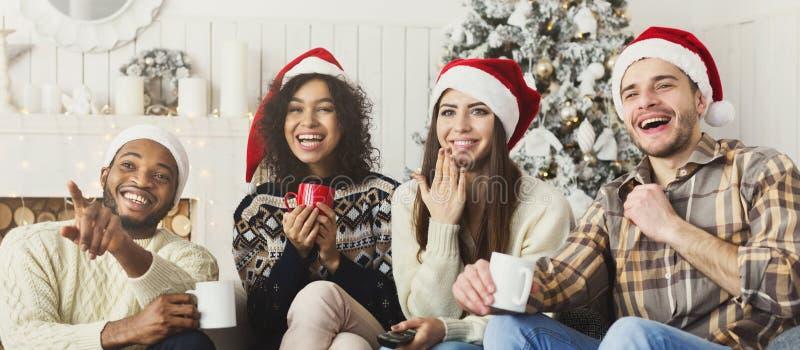 Amigos que miran película y que se divierten en la Nochebuena imagenes de archivo