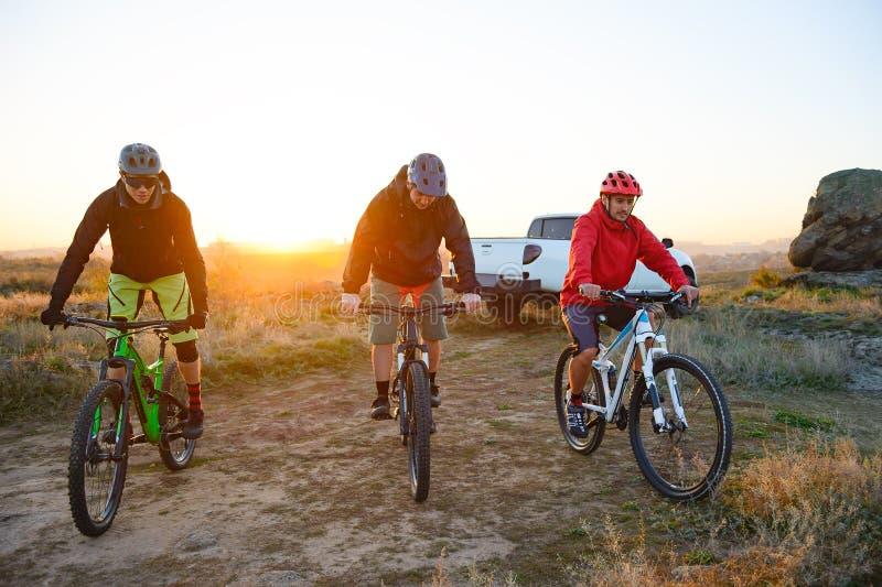 Amigos que montam bicicletas nas montanhas na frente do caminhão de Off Road do recolhimento no por do sol Conceito da aventura e imagem de stock