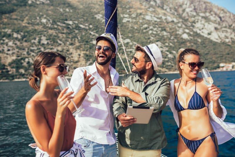 Amigos que navegam no iate usando a tabuleta digital Férias, curso, mar, amizade e conceito dos povos fotografia de stock