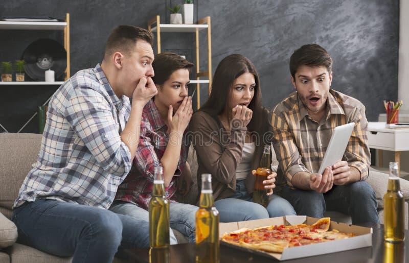 Amigos que olham o filme de terror na tabuleta digital em casa imagem de stock
