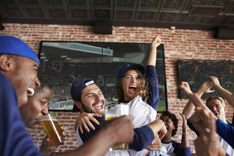 Amigos que olham o jogo na barra de esportes nas telas que comemoram foto de stock royalty free