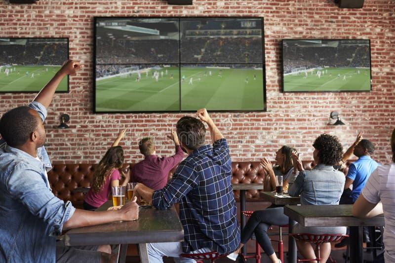Amigos que olham o jogo na barra de esportes nas telas que comemoram fotografia de stock royalty free