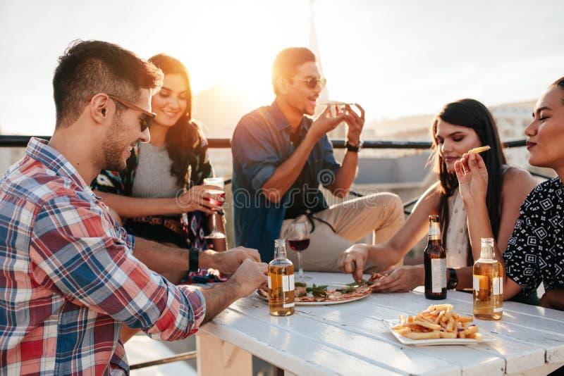 Amigos que partying e que comem a pizza fotografia de stock royalty free
