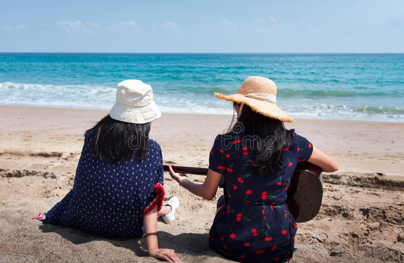 Amigos que pasan tiempo en la playa con una guitarra imagen de archivo