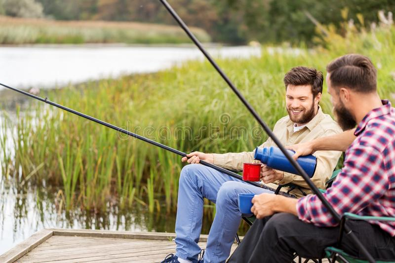 Amigos que pescam e que bebem o ch? da garrafa t?rmica fotos de stock