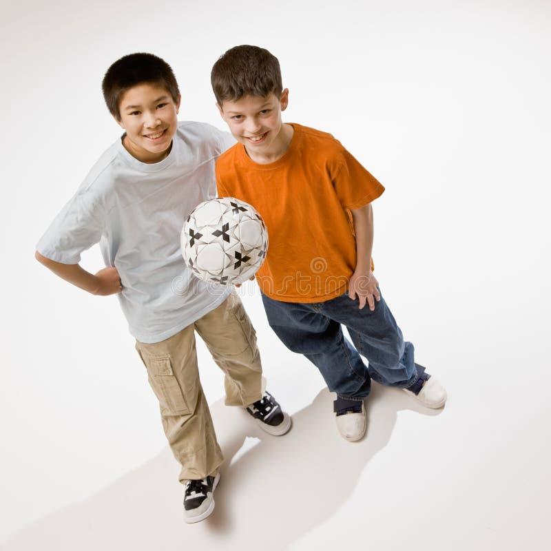 Amigos que prendem a esfera de futebol imagem de stock