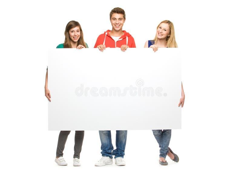 Amigos que prendem o poster em branco foto de stock