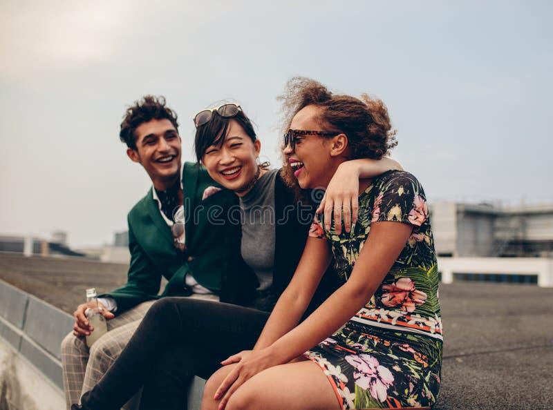 Amigos que ríen junto en tejado imágenes de archivo libres de regalías