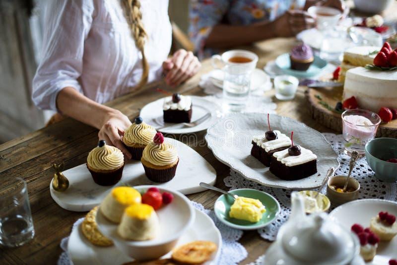 Amigos que recolectan junto en el disfrute h de las tortas de la consumición de la fiesta del té imagen de archivo libre de regalías