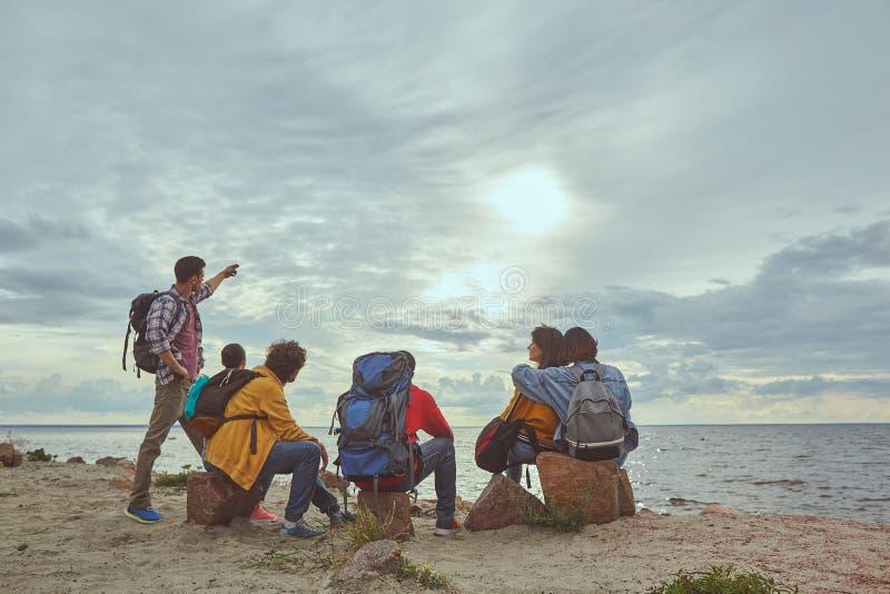 Amigos que recolectan y que miran paisaje del mar fotos de archivo
