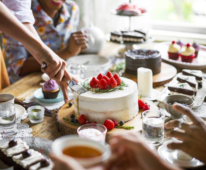 Amigos que recolhem junto na apreciação h dos bolos comer do tea party foto de stock royalty free
