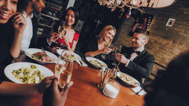 Amigos que refrigeram para fora a apreciação da refeição no restaurante fotografia de stock