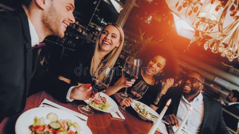 Amigos que refrigeram para fora a apreciação da refeição no restaurante fotos de stock