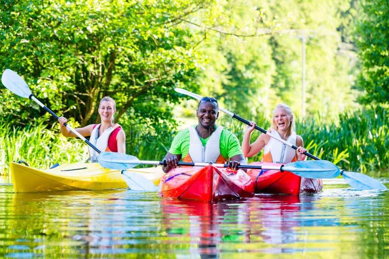 Amigos que se baten con la canoa en el río foto de archivo