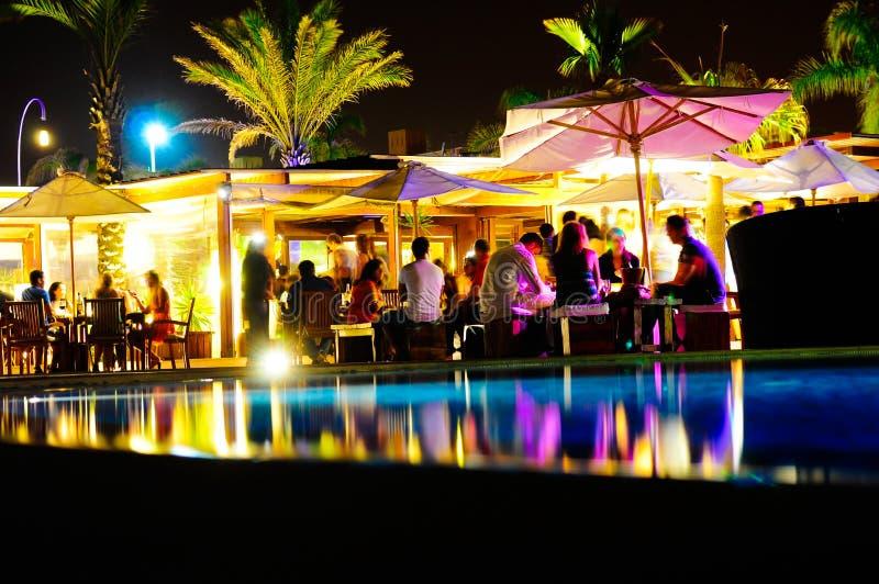 Amigos que se divierten, al aire libre piscina de la terraza del club nocturno y de la barra, partido de la muchedumbre imagenes de archivo