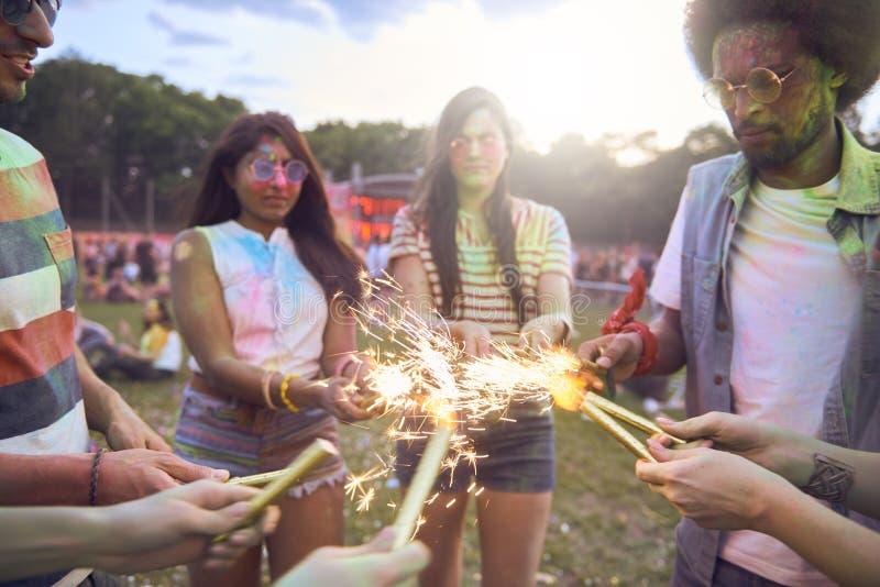 Amigos que se divierten con la bengala en el festival del verano fotografía de archivo