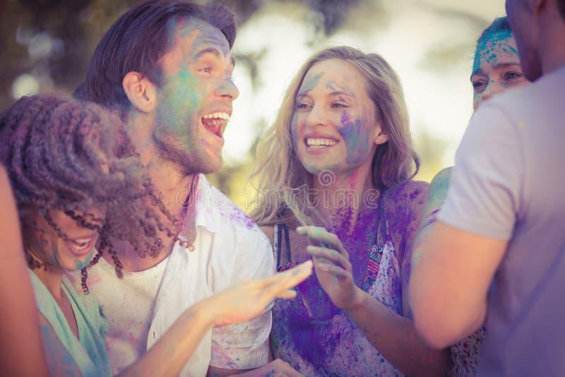 Amigos que se divierten con la pintura del polvo en el parque imagenes de archivo