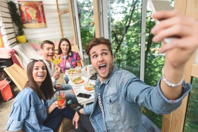 Amigos que se divierten durante almuerzo junto imagen de archivo libre de regalías