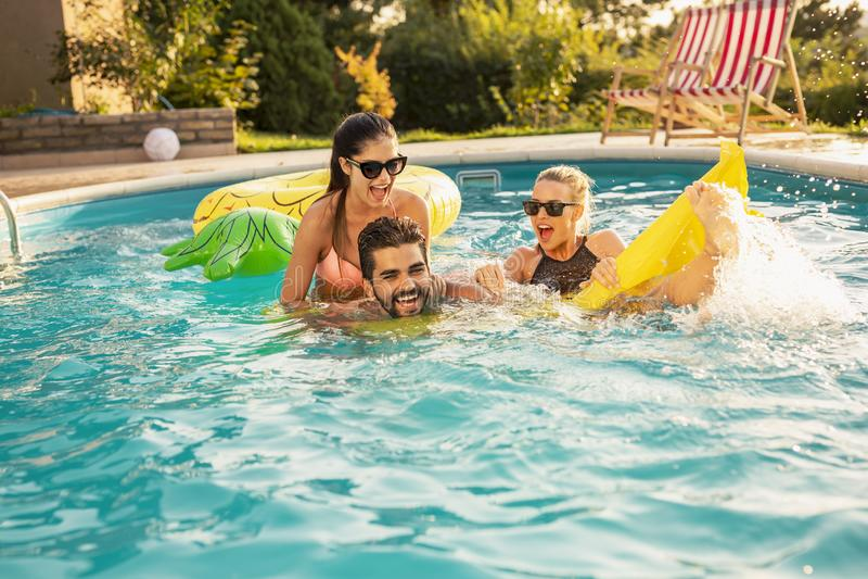 Amigos que se divierten en la piscina fotos de archivo libres de regalías