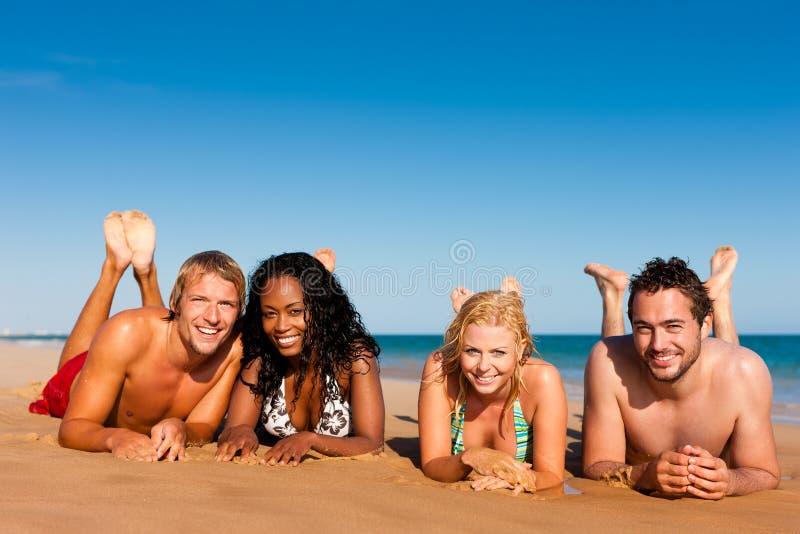 Amigos que se ejecutan el vacaciones de la playa imagenes de archivo